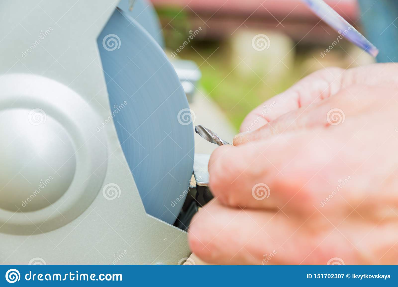 Close up of Industrial worker sharpening drill with grindstone abrasive disc cutter machine