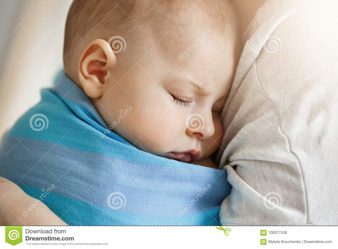 Close up portrait of innocent little child, sleeping on mother hands in blue baby sling. Quite and relaxing scene
