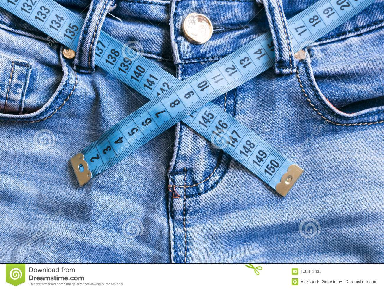 Close up jeans and soft meter waist measurement.