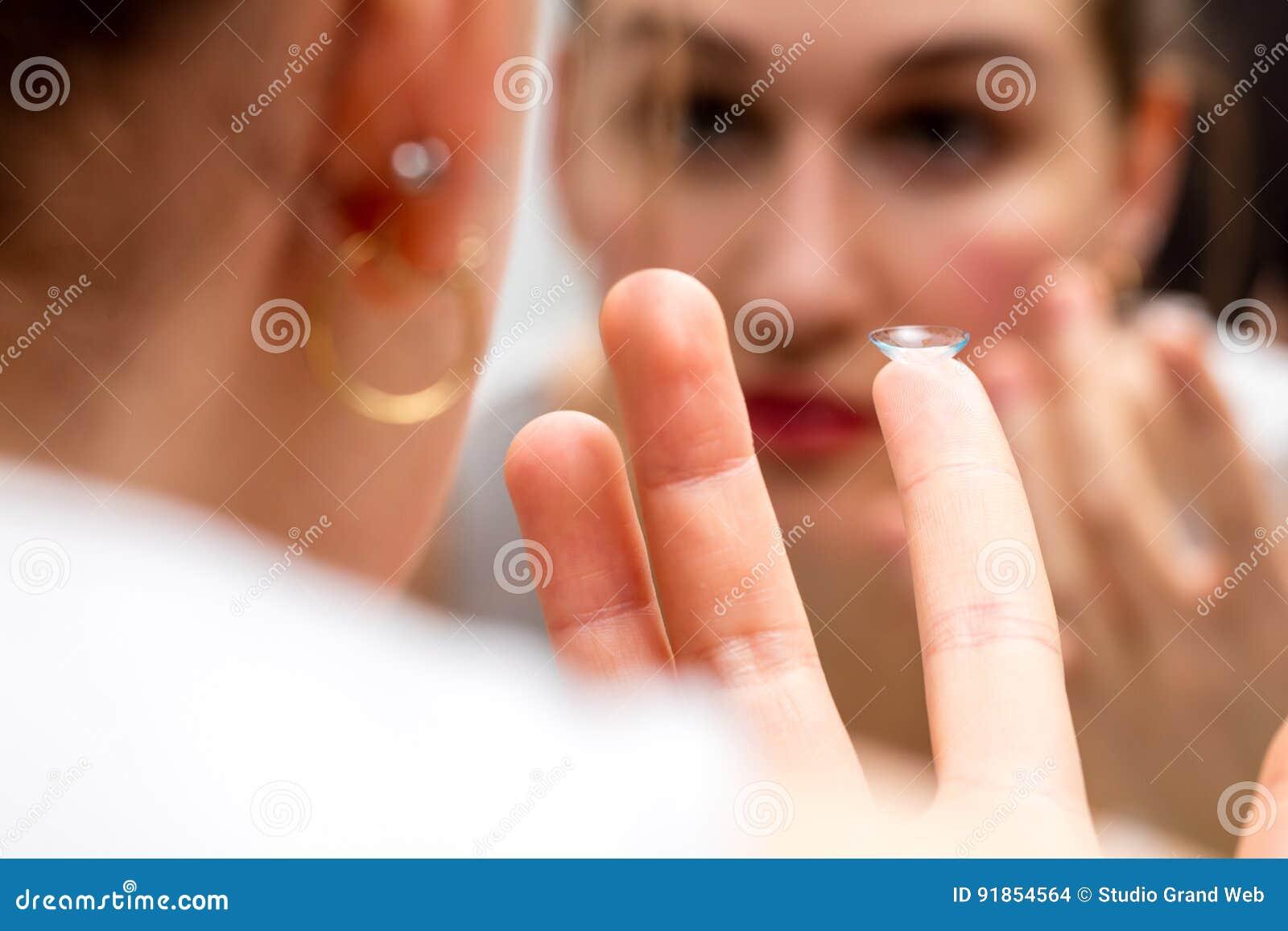 Close-up, jonge vrouw met een contactlens die in spiegel kijken