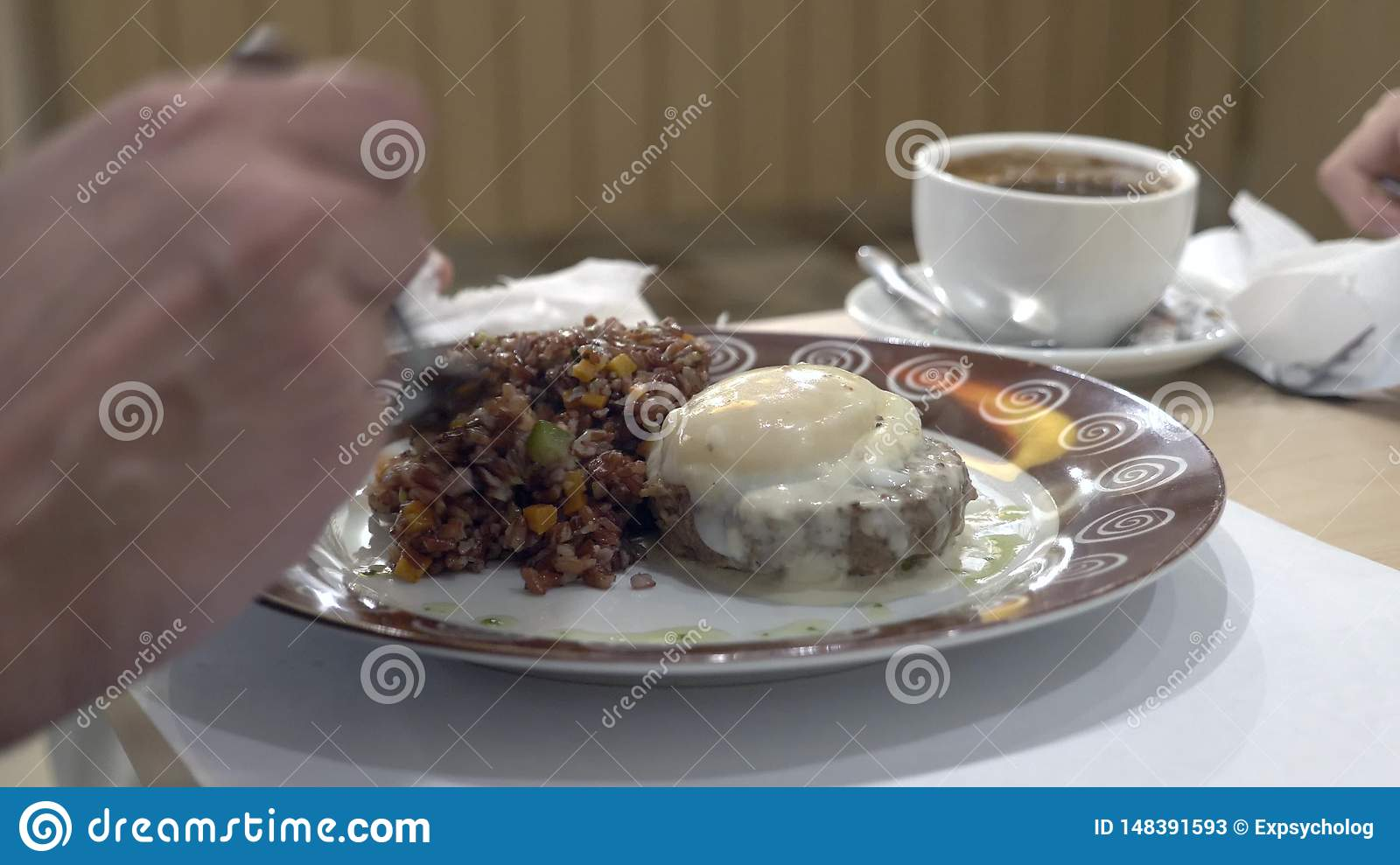 Close-up. 4k. the man eats red rice with beef steak and egg poached, with vegetables.