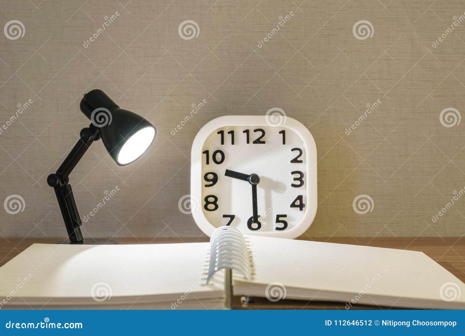 Kinderwekker Met Licht : Close up kleine lamp met licht met vaag boek en witte wekker op