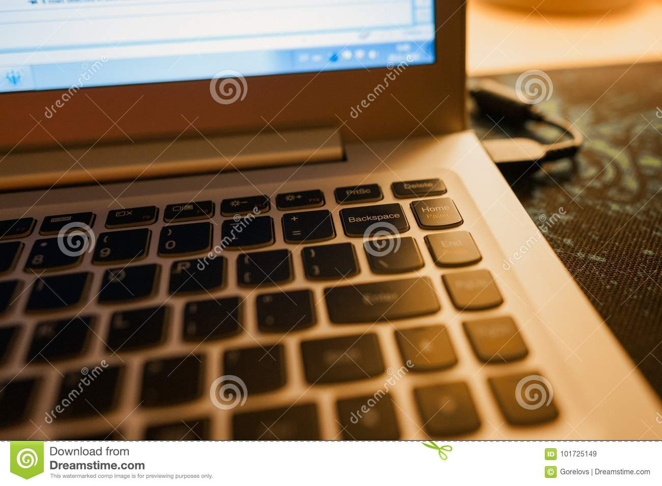 Close-up of laptop keyboard with focus on Backspace button and highlighted with warm evening light