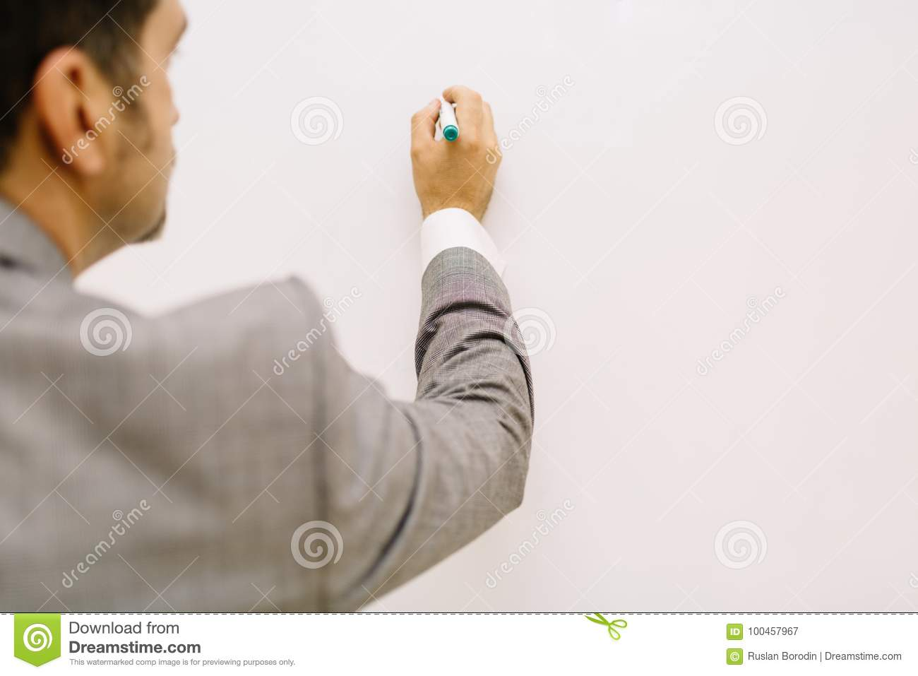 Teacher with a multimedia projector. Close-up businessman writing on a desk background. Lecture concept. Copy space.