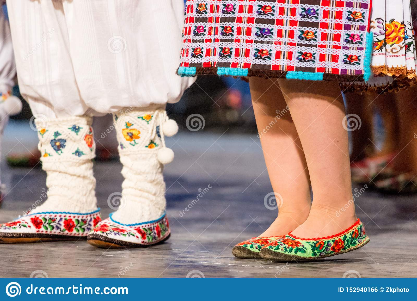 Close up of legs of young Romanian dancers perform a folk dance in traditional folkloric costume. Folklore of Romania