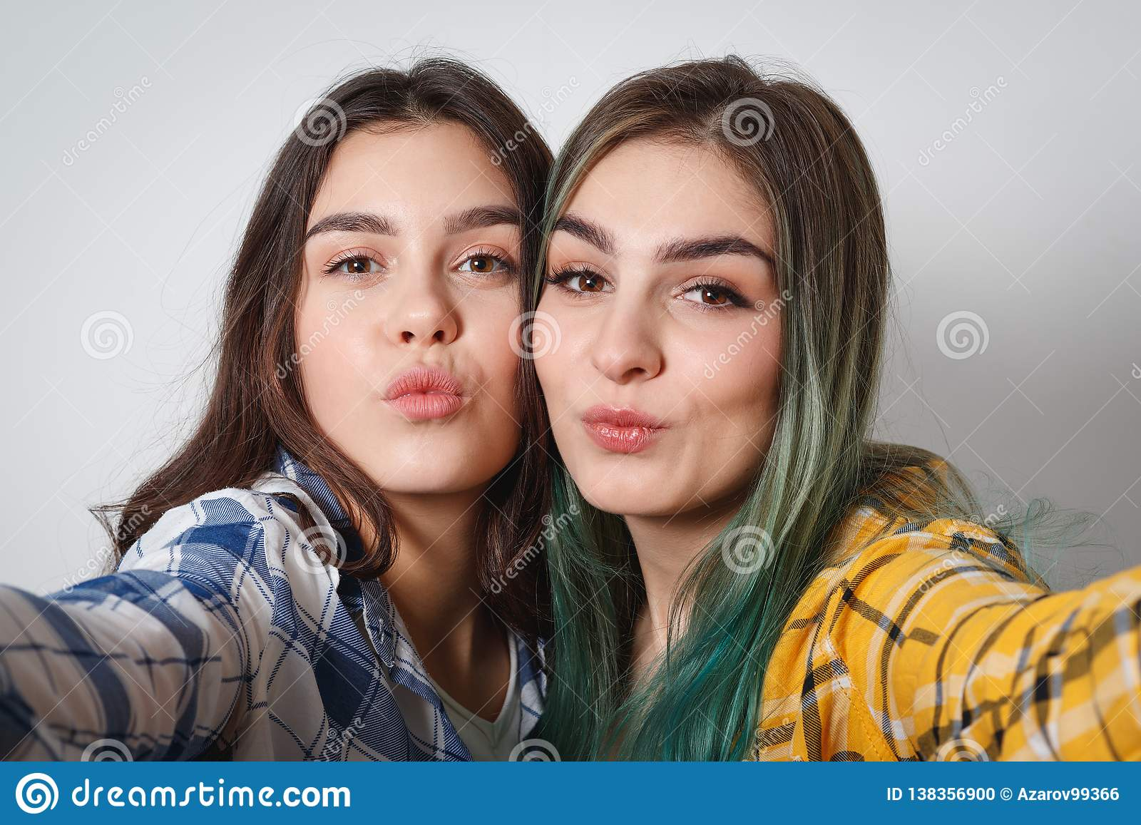 Close up lifestyle selfie portrait of two young positive woman having fun and making selfie, teenage hipster trendy clothes and