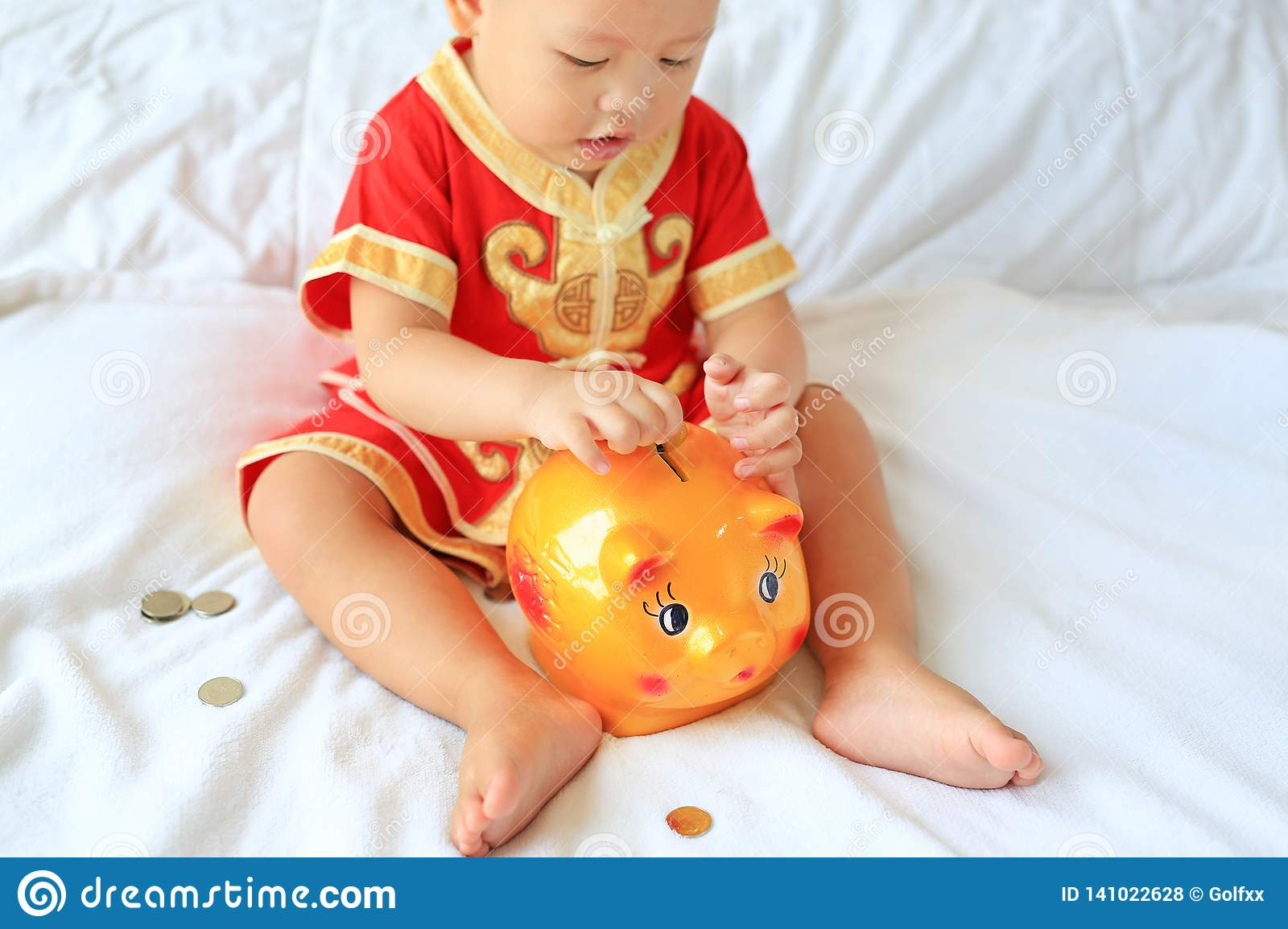 68e0abd9c064 Close up little Asian baby boy in traditional Chinese dress putting some  coins into a piggy
