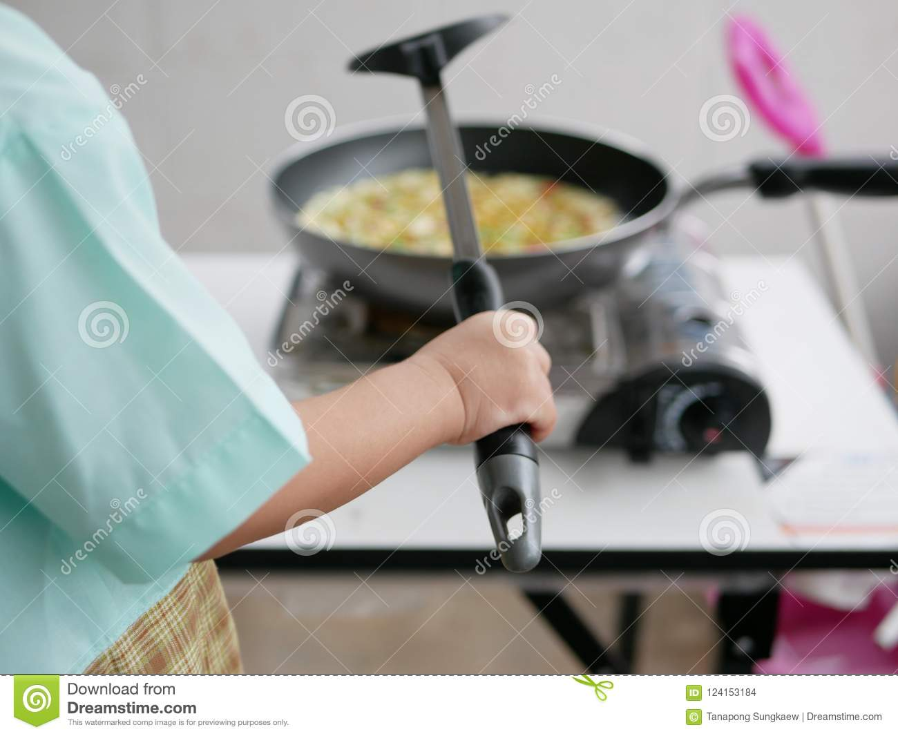 Close up of little Asian baby`s hand holding a spatula learning to cook food