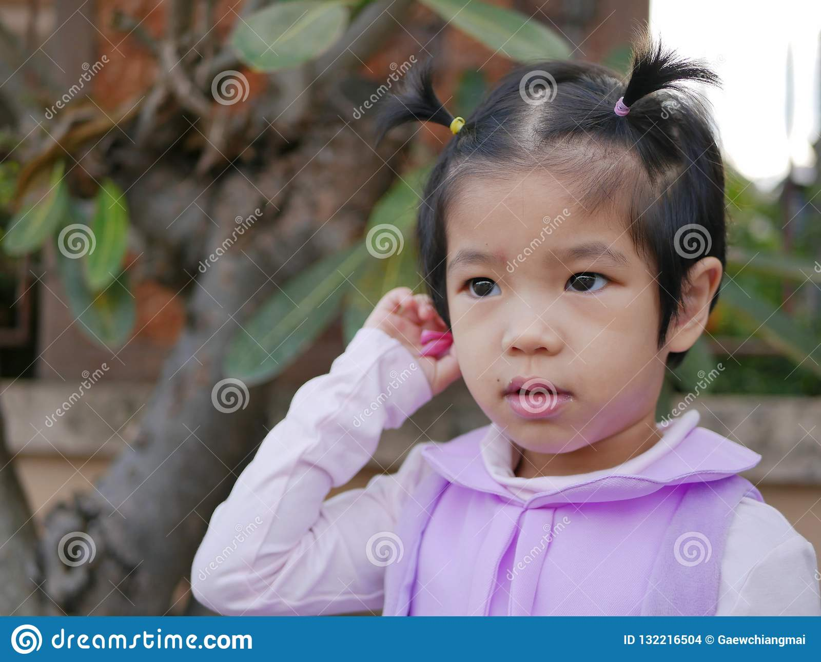 Close up of little Asian, Thai, baby girl, putting a flower behind her ear