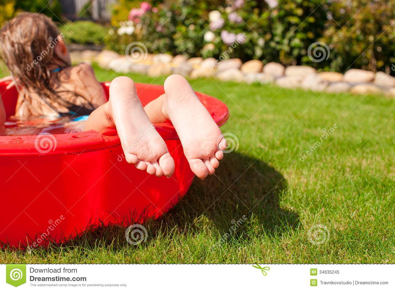 Close-up of a little girl s legs in small red pool