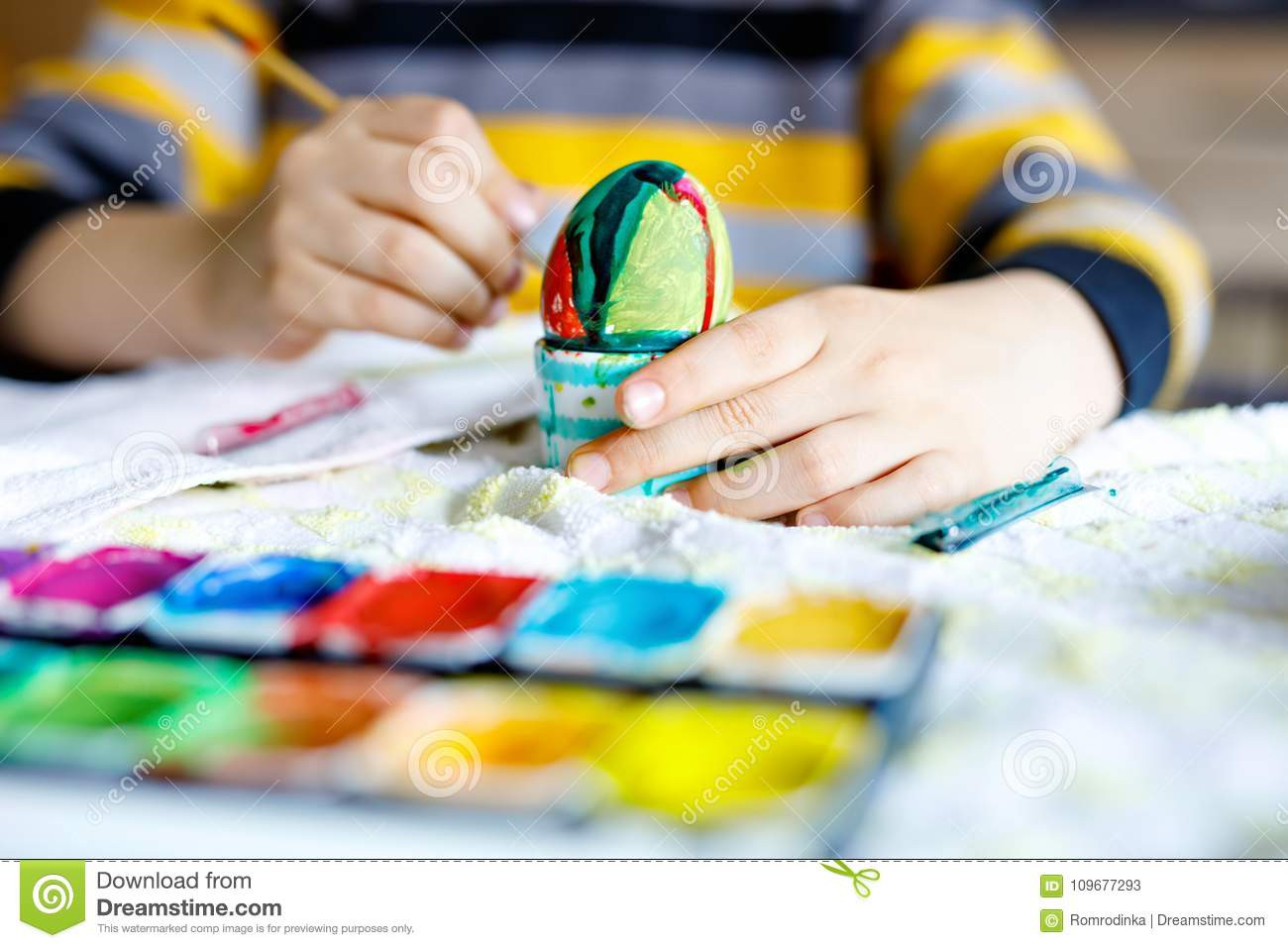 Close-up of little kid hands coloring eggs for Easter holiday