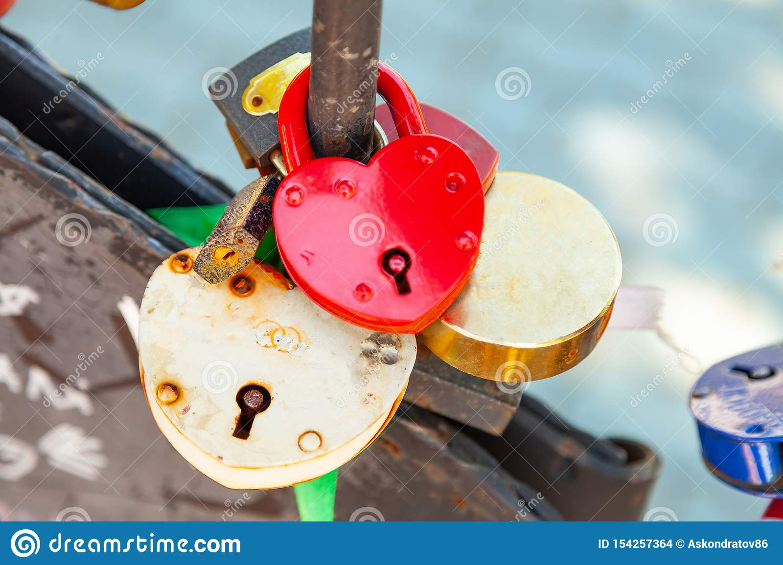 Close-up on locks of hearts in different colors and shapes hanging on the fence as a sign of eternal love, which is hung during
