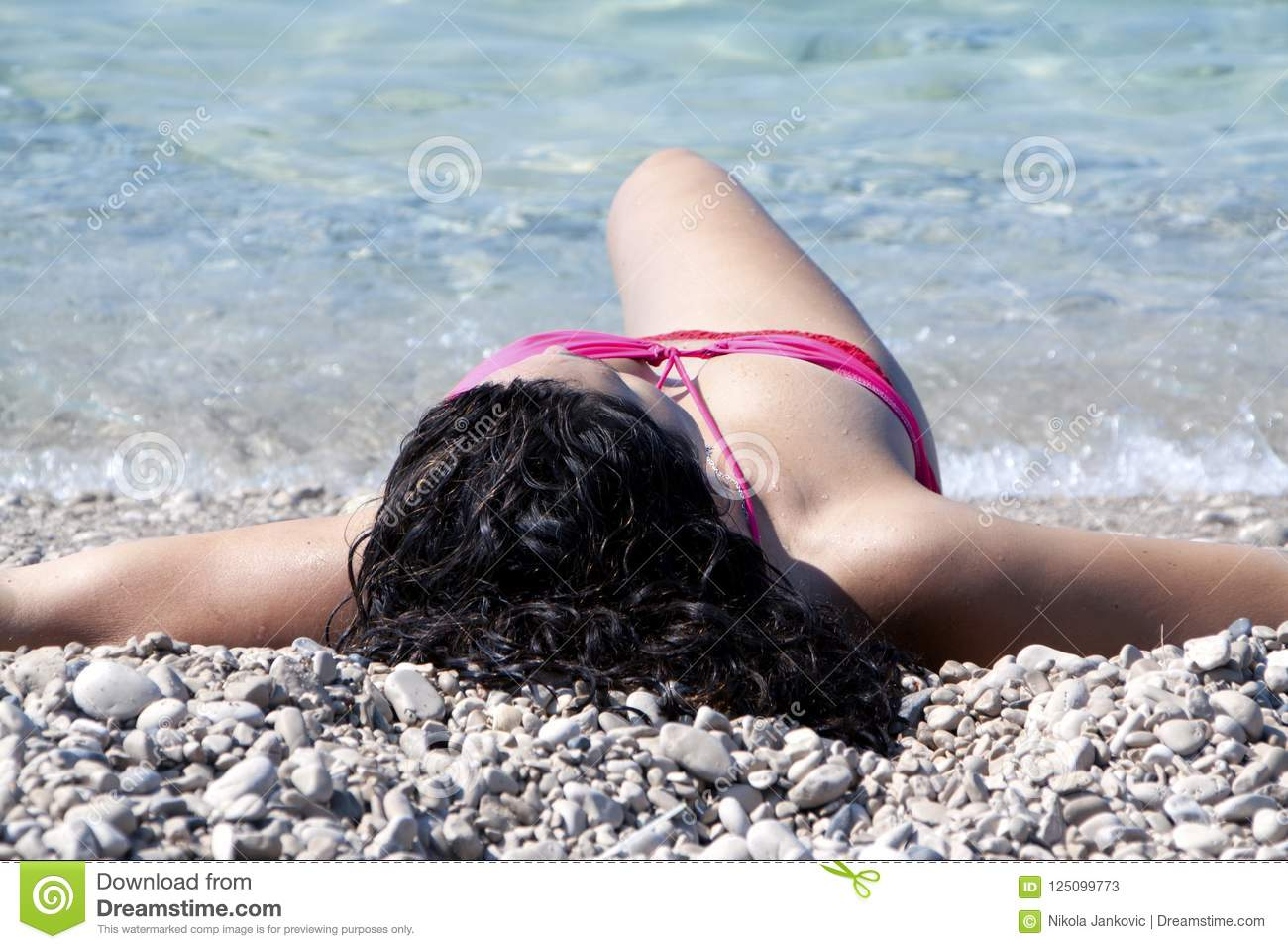 46b030a2209 Close up low angle view of Attractive black haired woman in red bikini  laying on the beach. More similar stock images