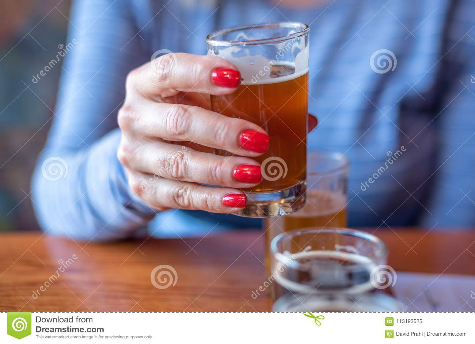 Close up macro da mulher que guarda um vidro do voo da cerveja
