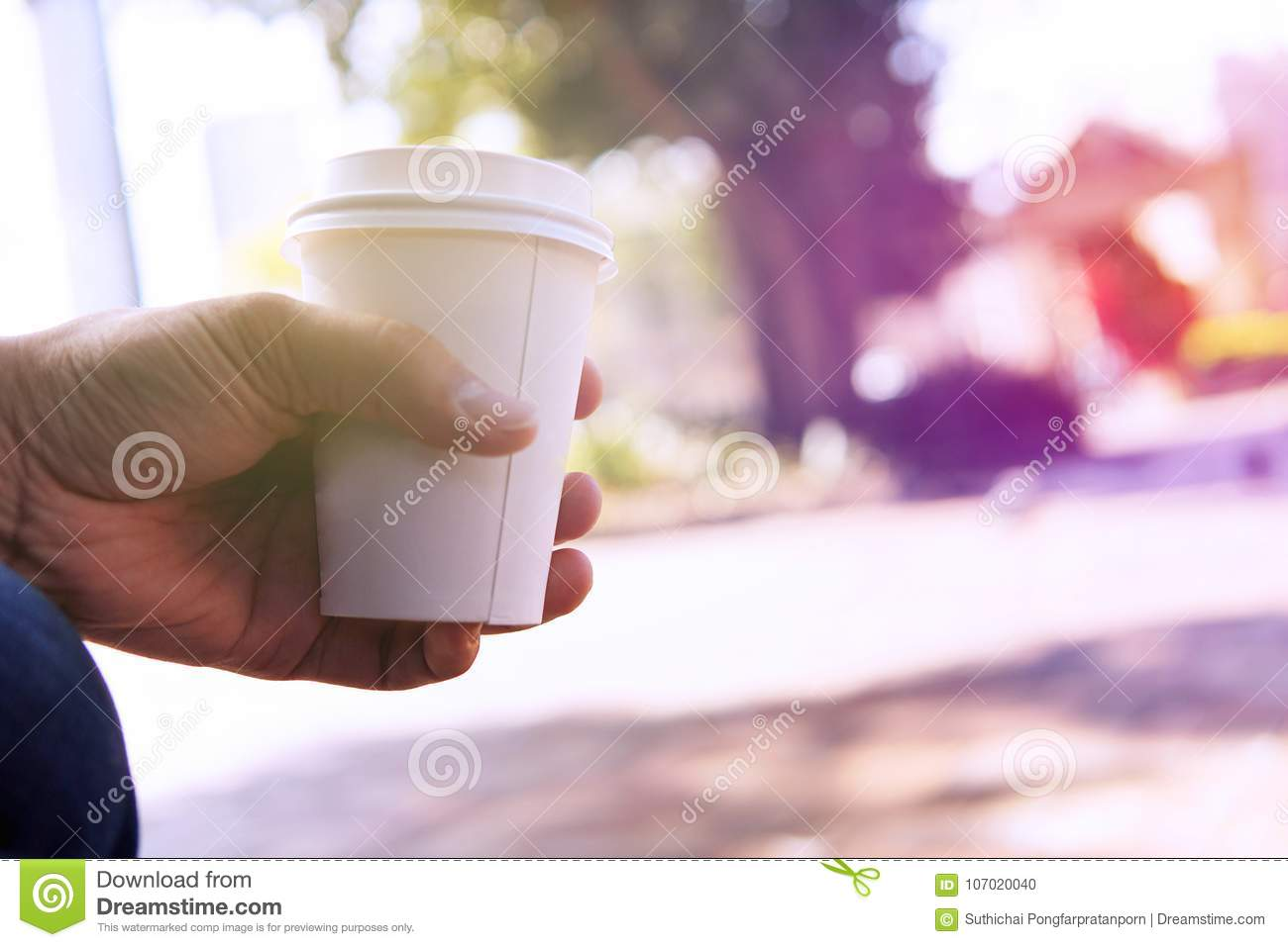 Close up of male hand holding take away coffee cup at morning ti