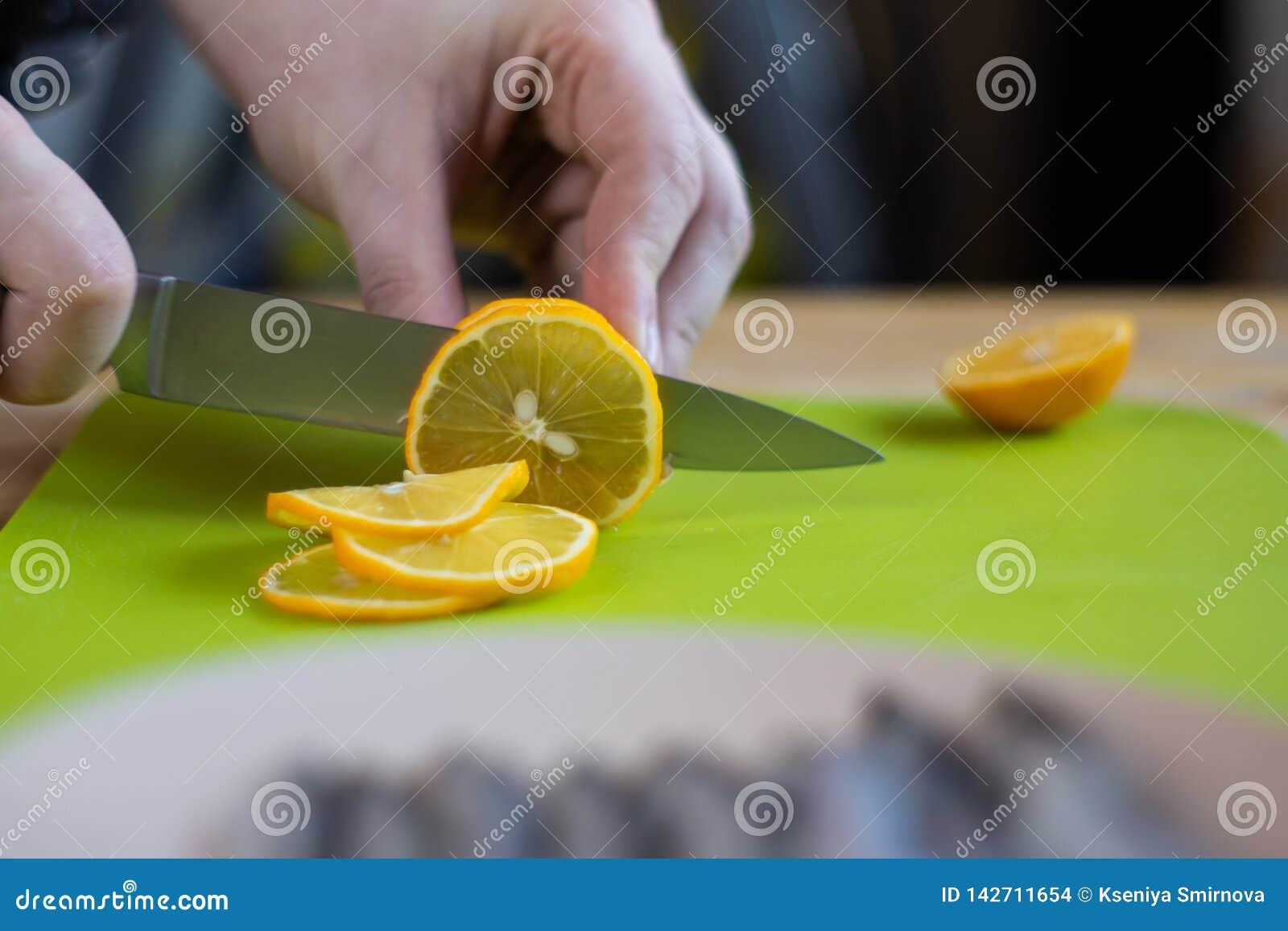 Male hands cut lemon on green cutting board, close up