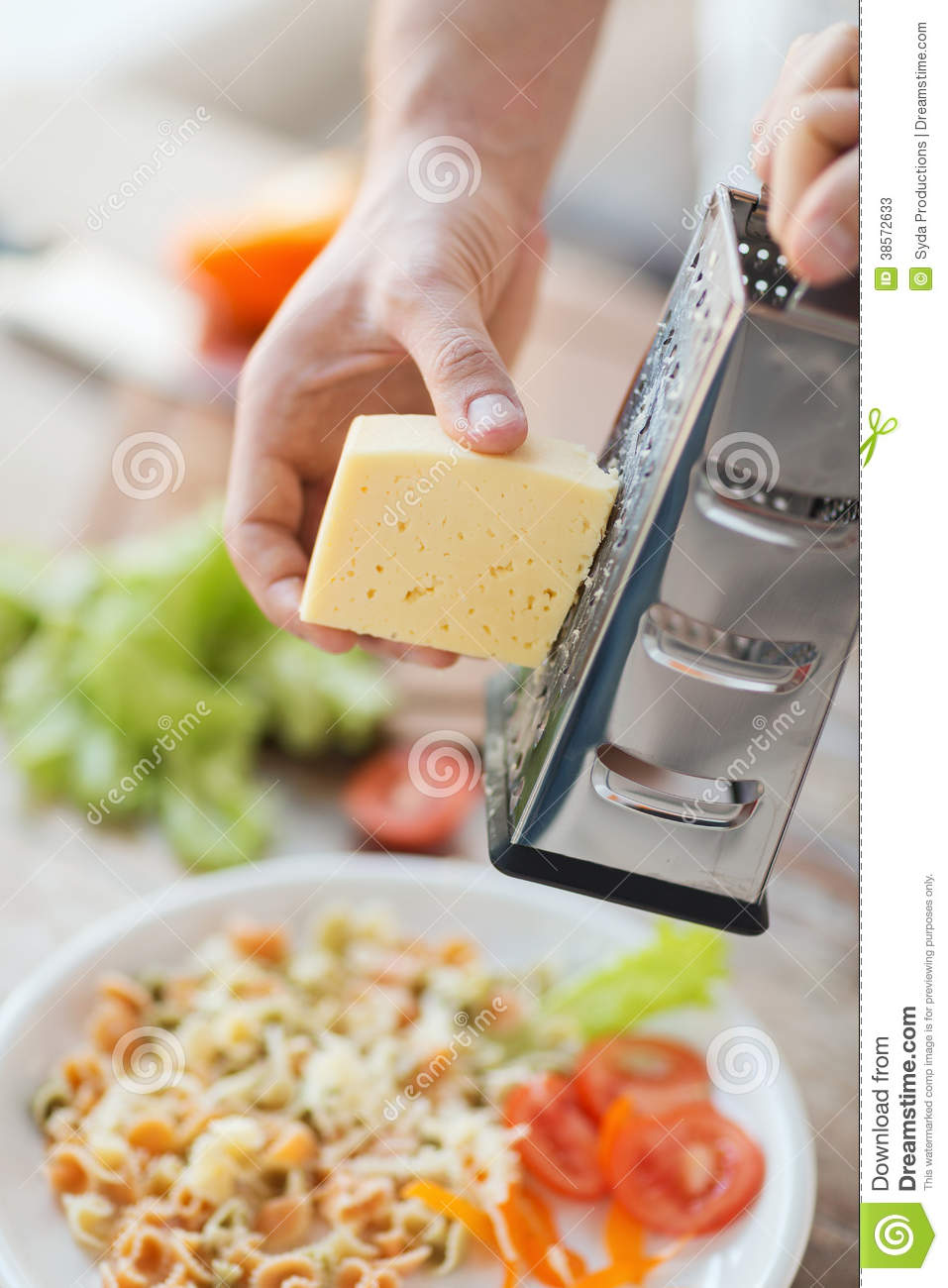 close up of male hands grating cheese over pasta stock photos image 38572633. Black Bedroom Furniture Sets. Home Design Ideas