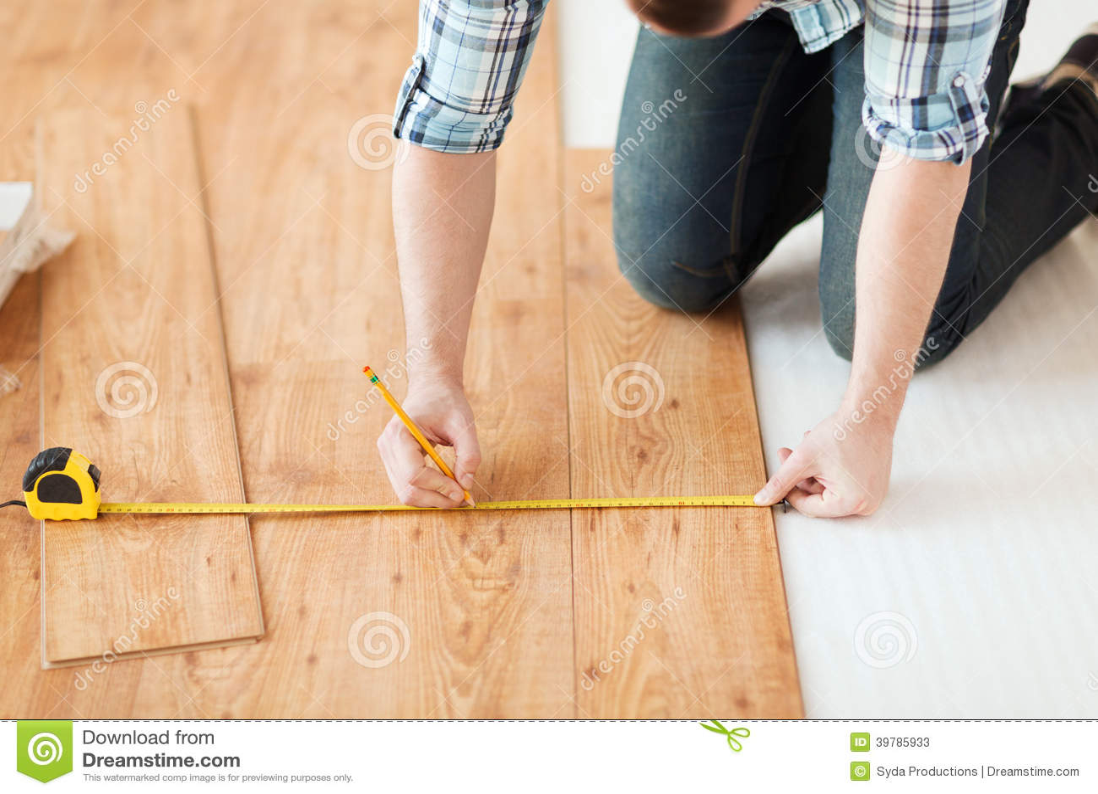 close up of male hands measuring wood flooring stock image. Black Bedroom Furniture Sets. Home Design Ideas