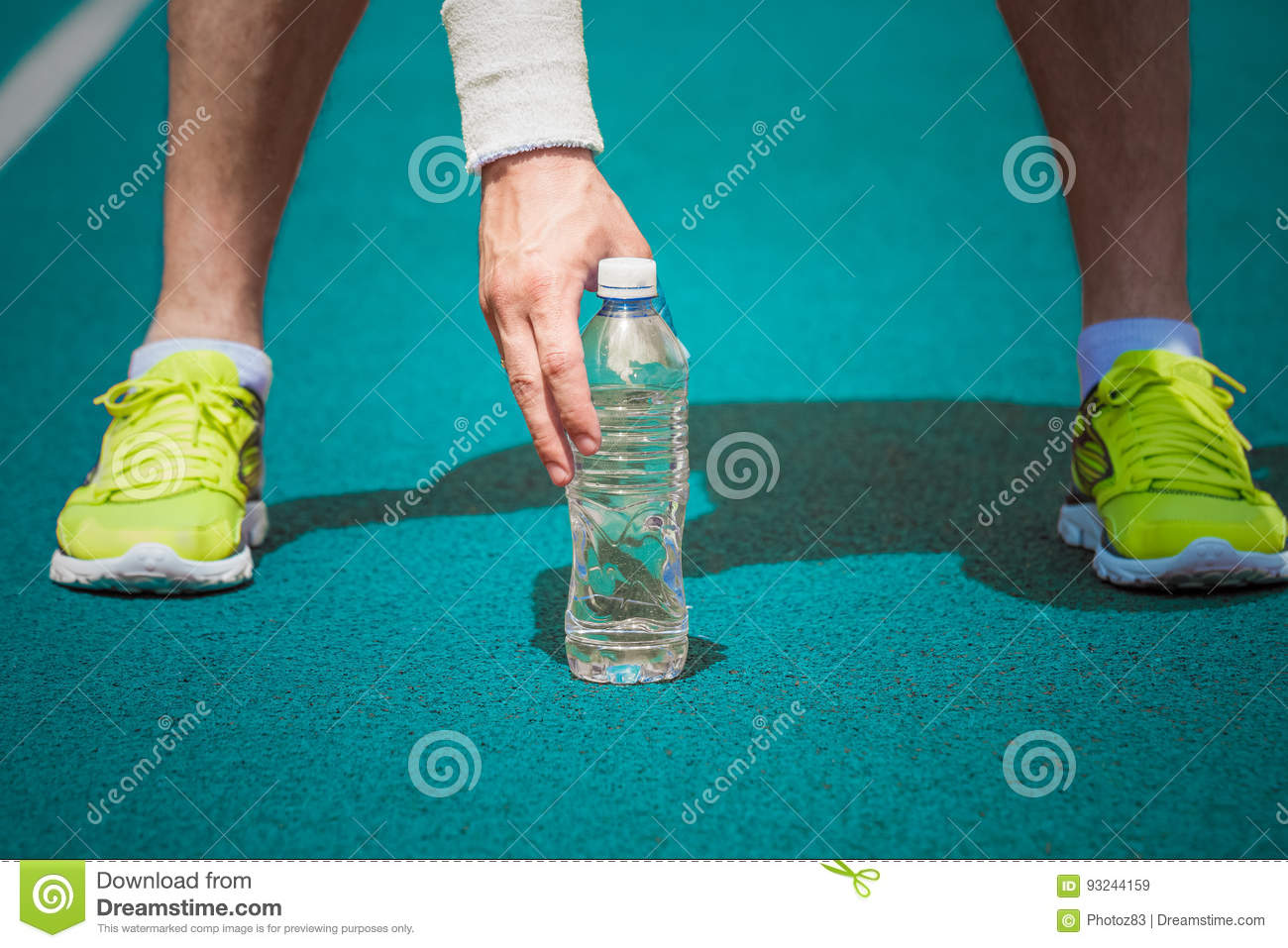Close up of male jogger holding plastic bottle of water on running track