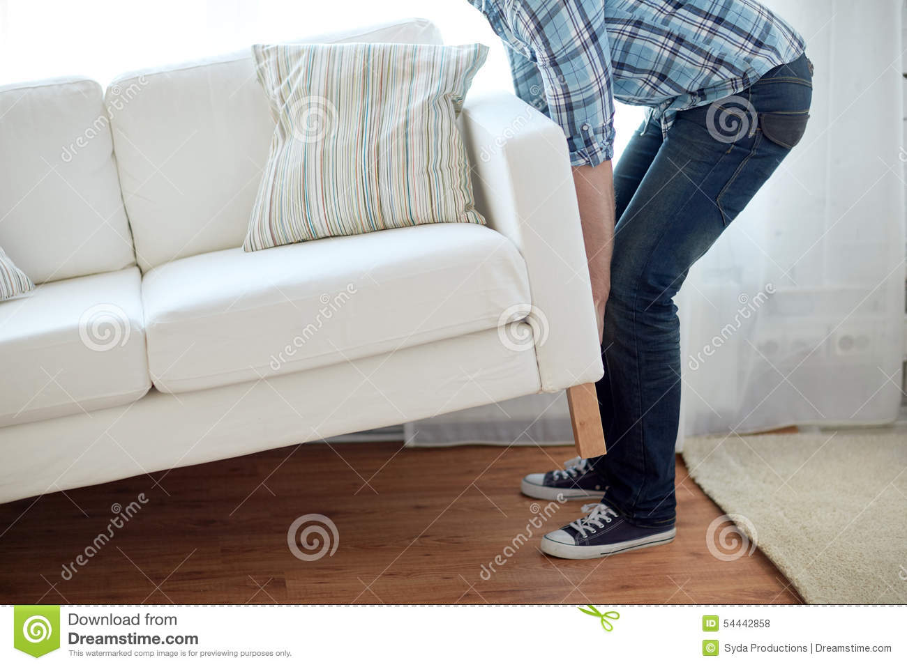Close Up Of Male Moving Sofa Or Couch At Home Stock Photo