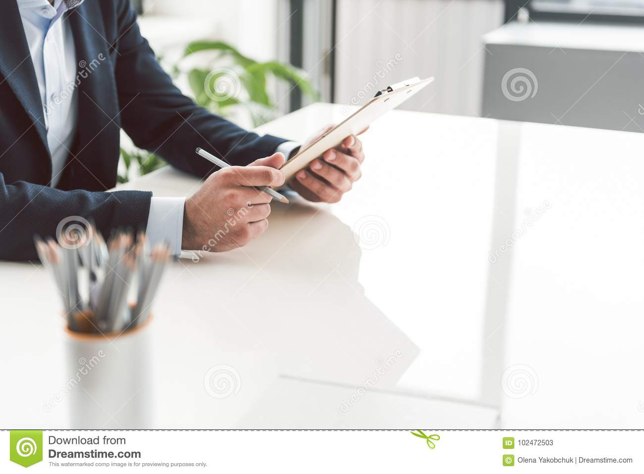 Male hands keeping clipboard at desk