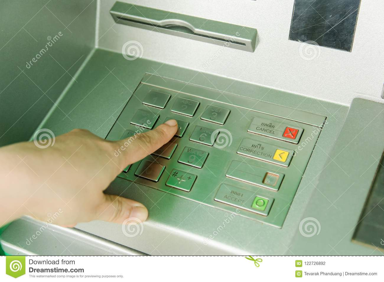 Close up of man hand entering password code on ATM bank machine
