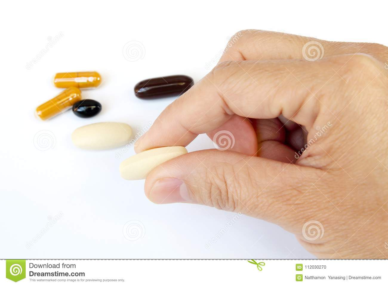 Close up the man hand holding vitamin or pill on white