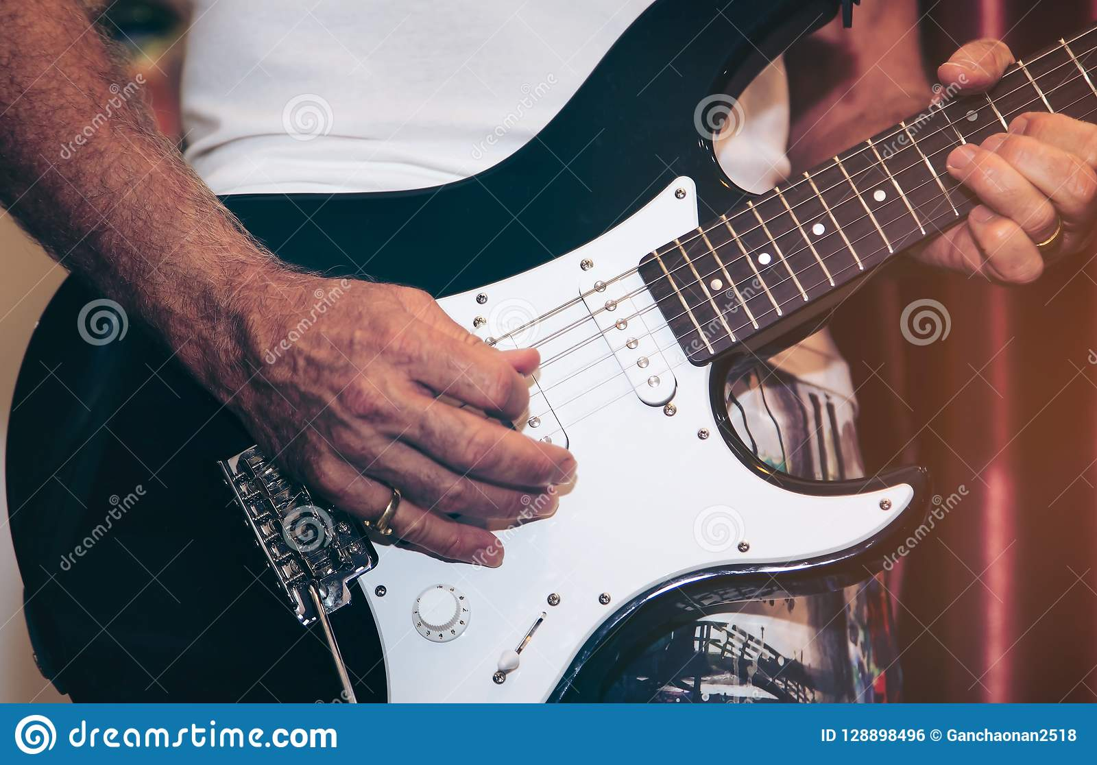 Close up of man hand playing guitar on stage for background.