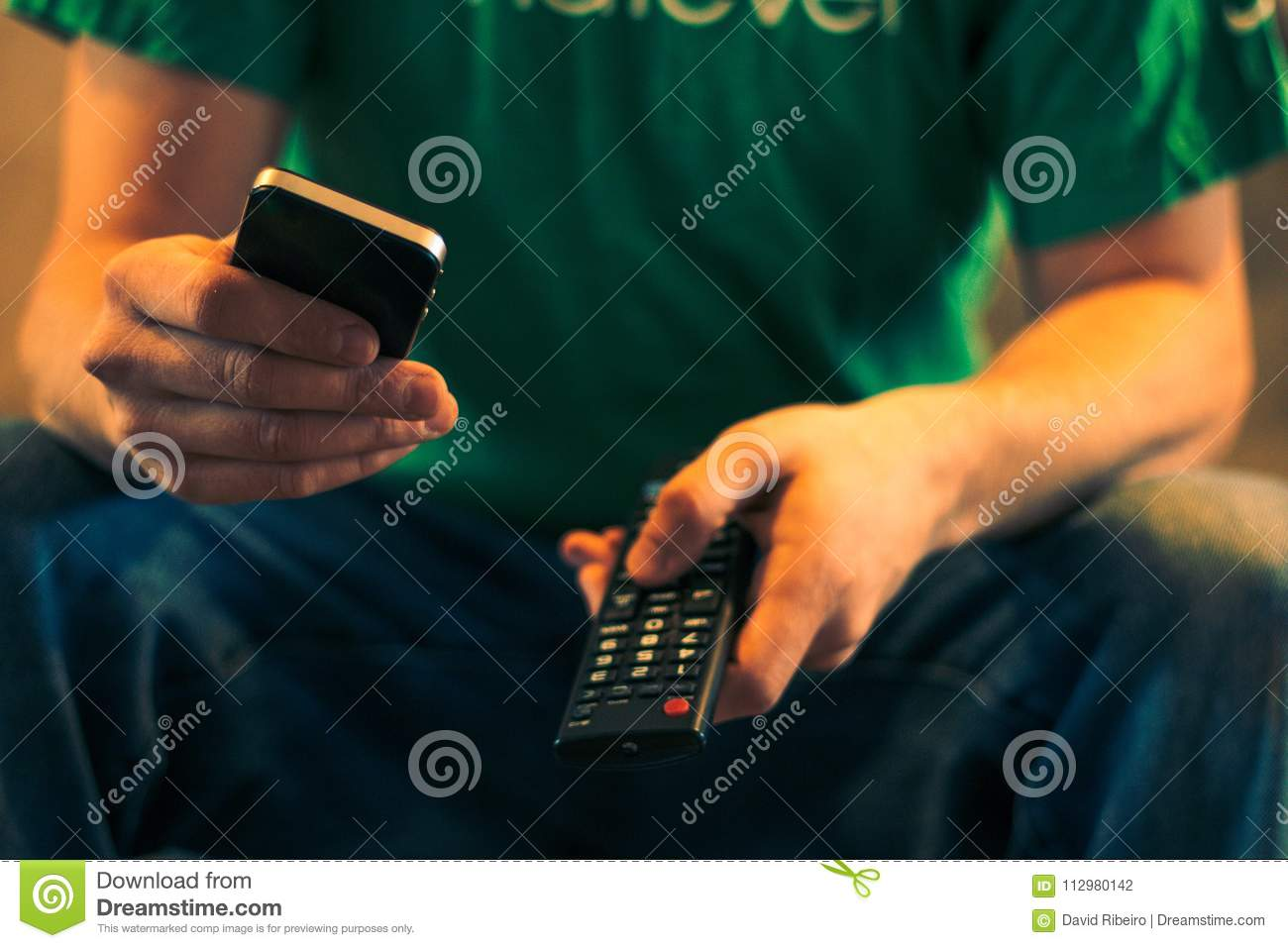 Close up of a man holding a cell phone and a tv remote control