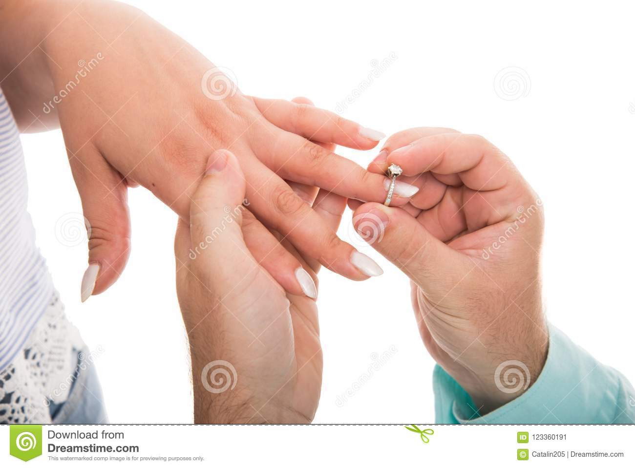 Close Up Of Man Putting Engagement Ring On Girlfriend Finger Stock