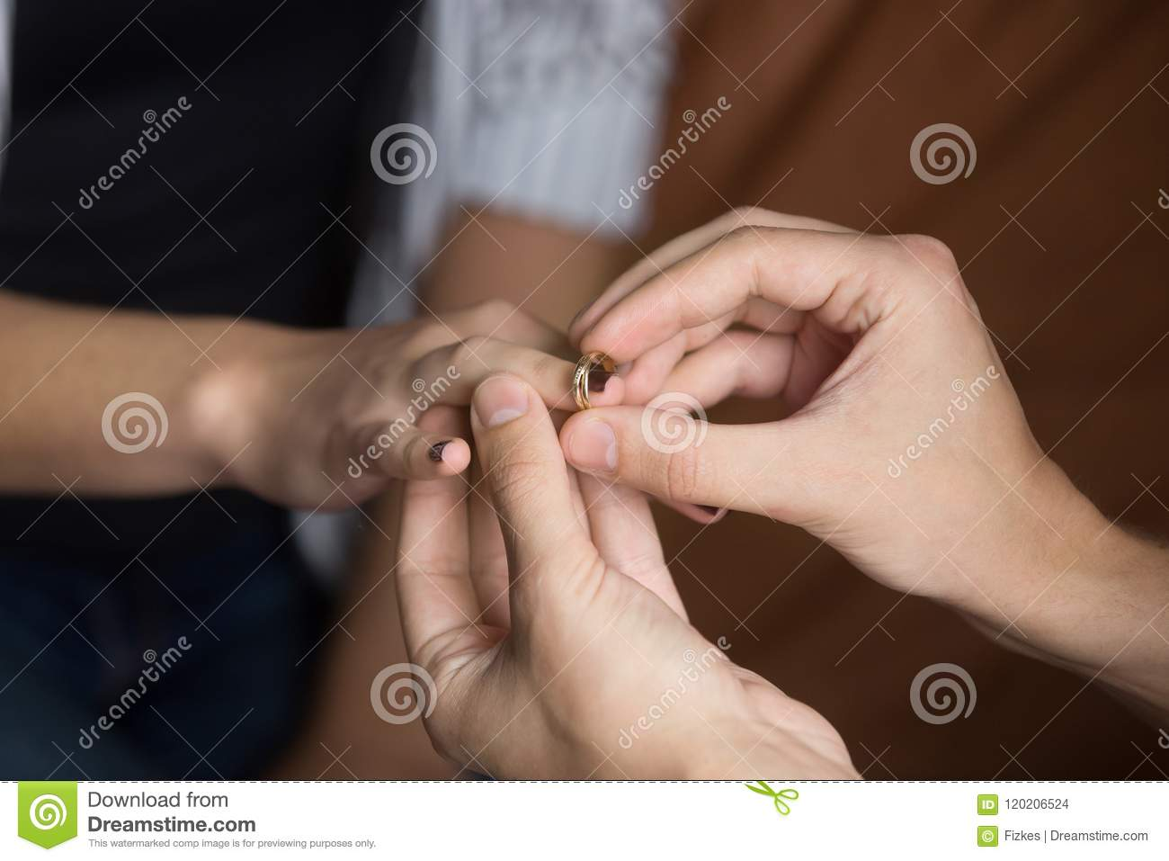 Close Up Of Man Putting Wedding Ring On Woman Finger Stock Photo