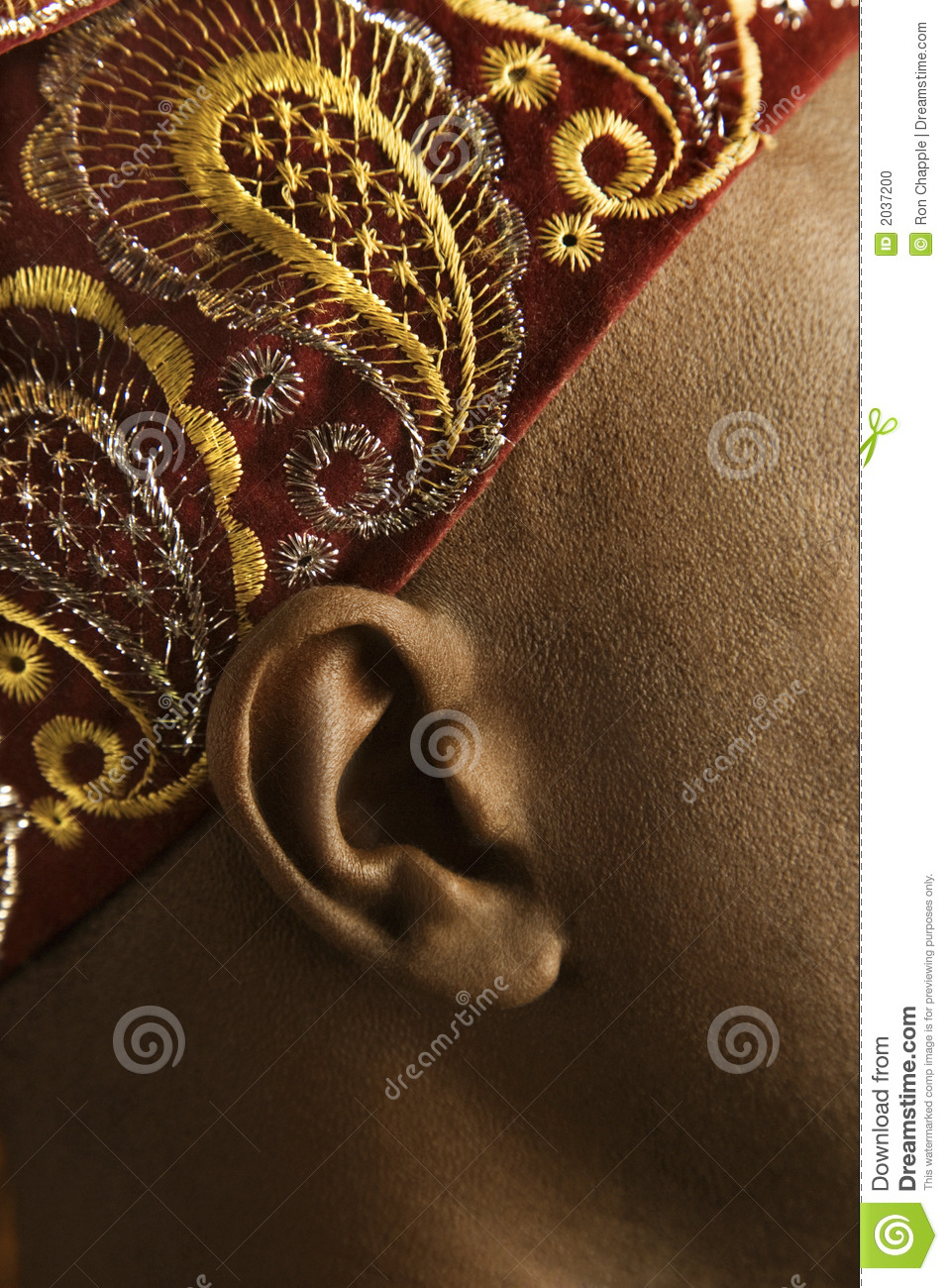 Close-up of man s ear and African hat.