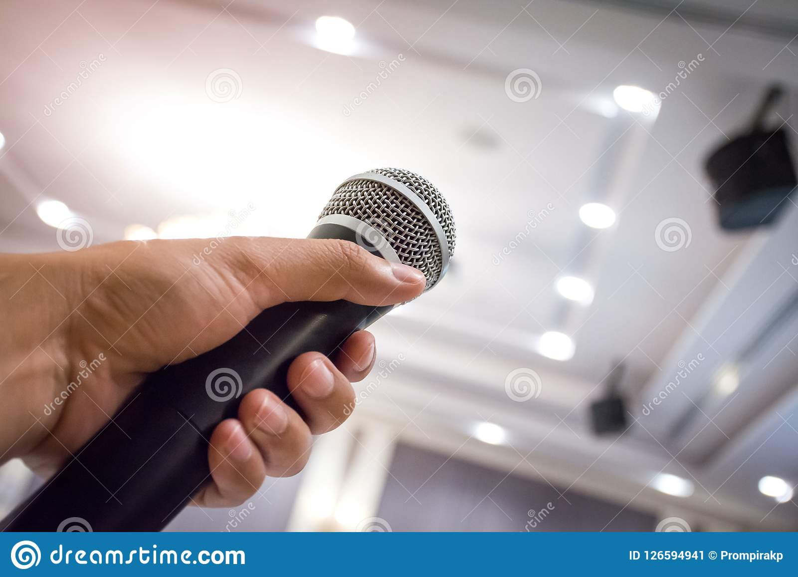 Close up of man`s hand holding microphone in conference hall or