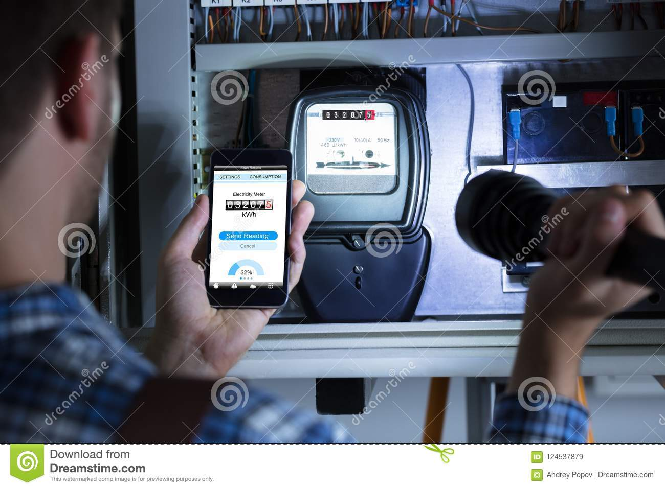 Man`s Hand Holding Mobile Phone Showing Electric Meter Reading Stock