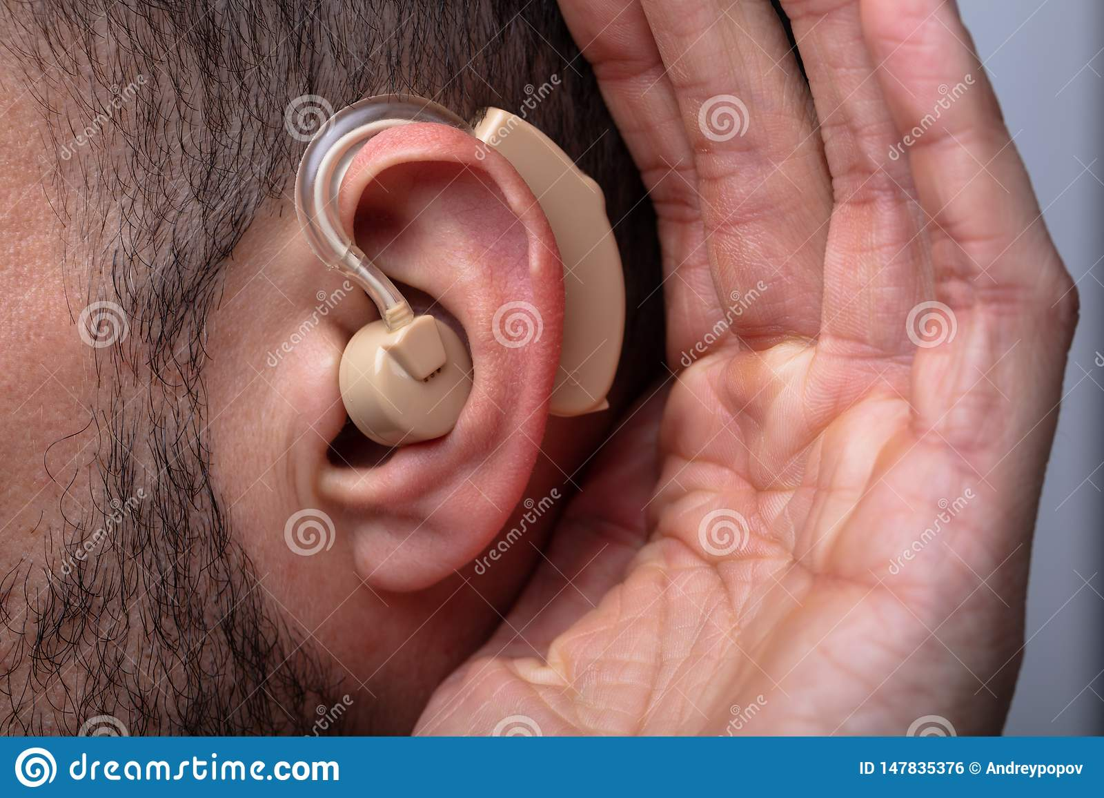 Man Inserting Hearing Aid In His Ear