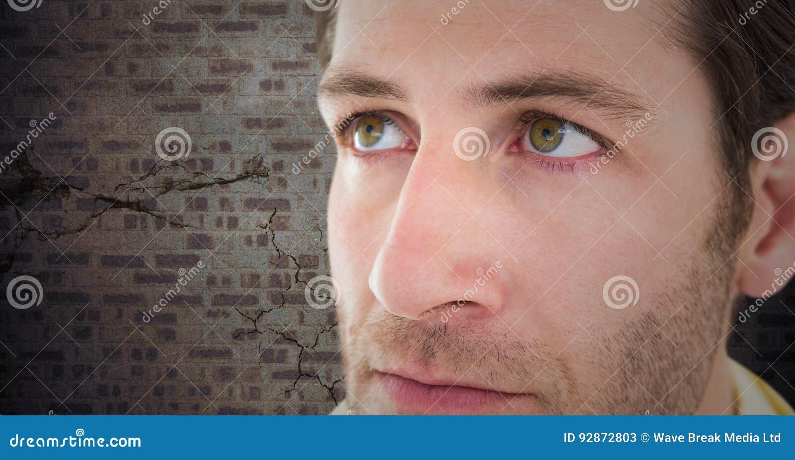 Close up of man`s sad face against brown brick wall