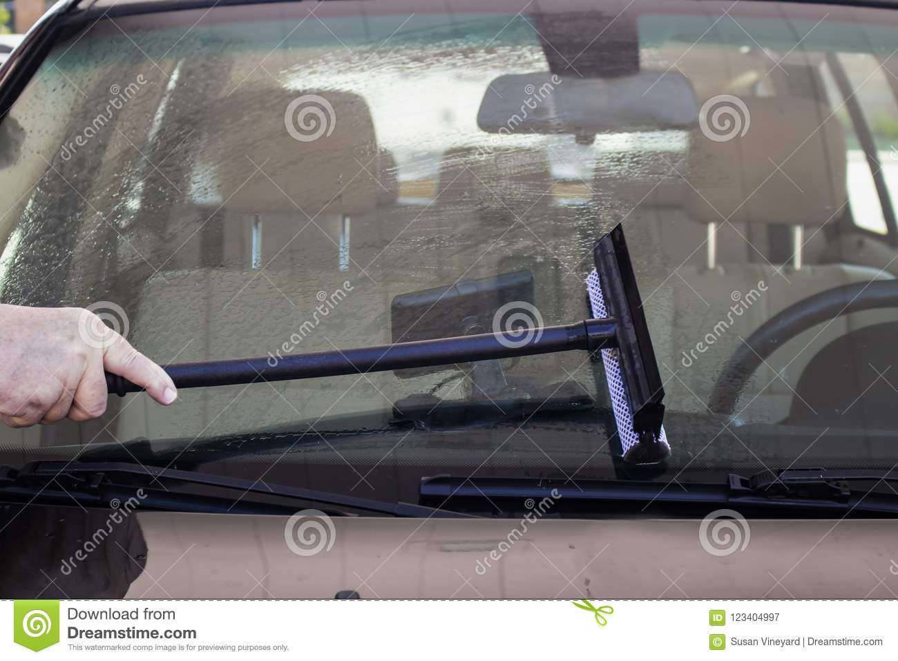 Close-up of man using squeegee to clean the windshield of a car with a GPS visable inside on dash