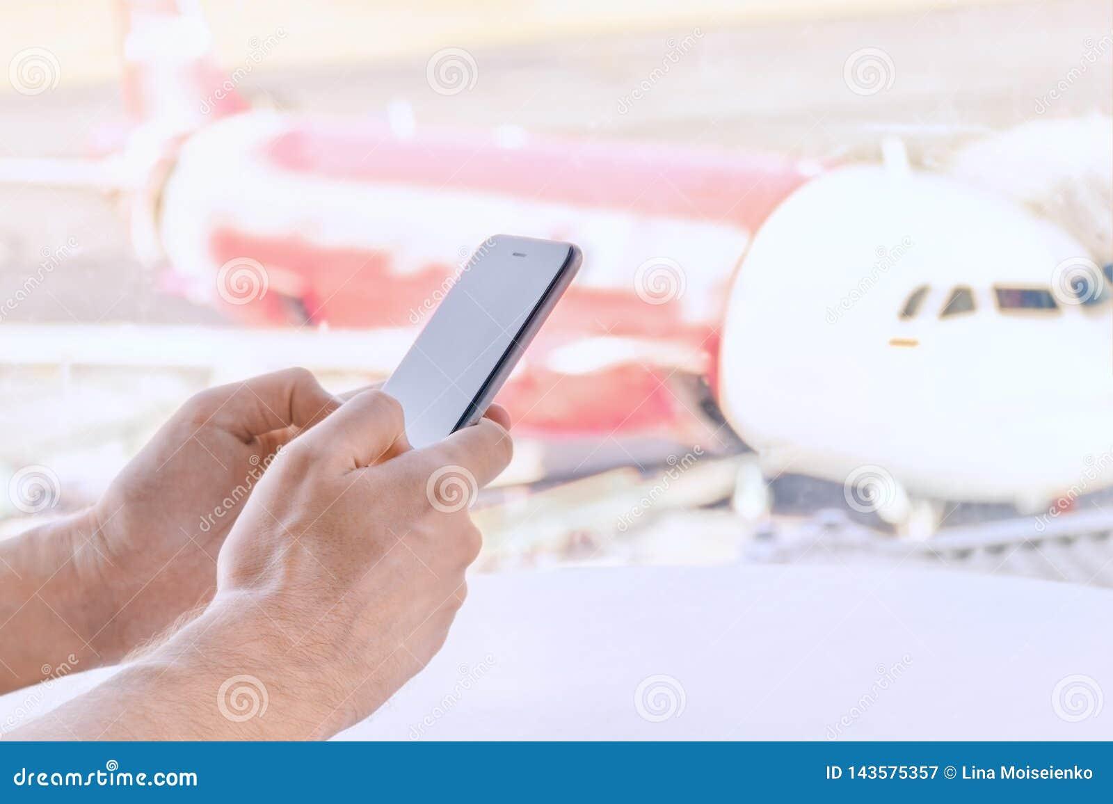 Close-up, mannelijke handen die een mobiele telefoon, luchthaven onscherpe achtergrond houdt