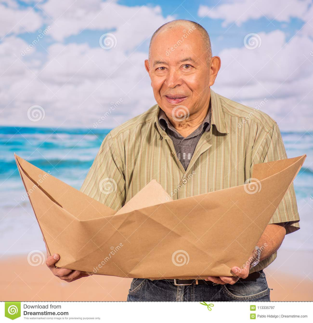 Close up of mature man with brown paper origami boat, concept for aspirations, leadership, strategy or just boredom in