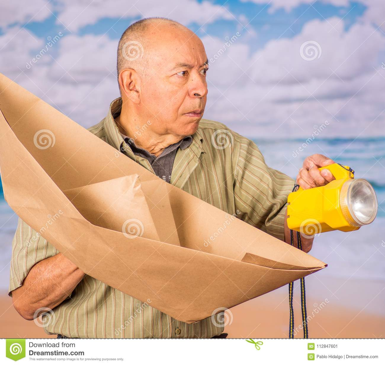 Close up of mature man with brown paper origami boat and yellow lantern, concept for aspirations, leadership, strategy