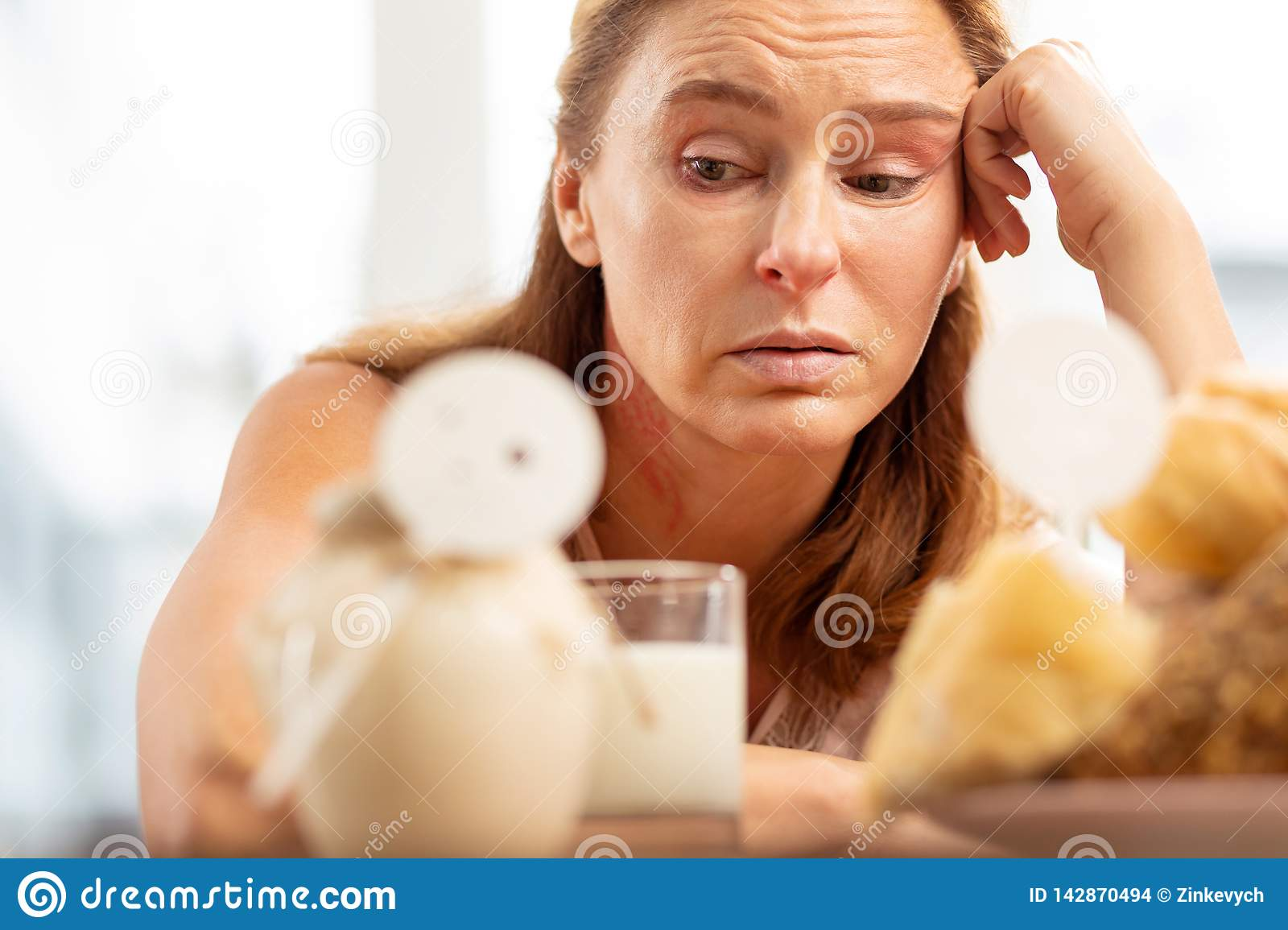 Close up of mature woman with facial wrinkles having food allergy