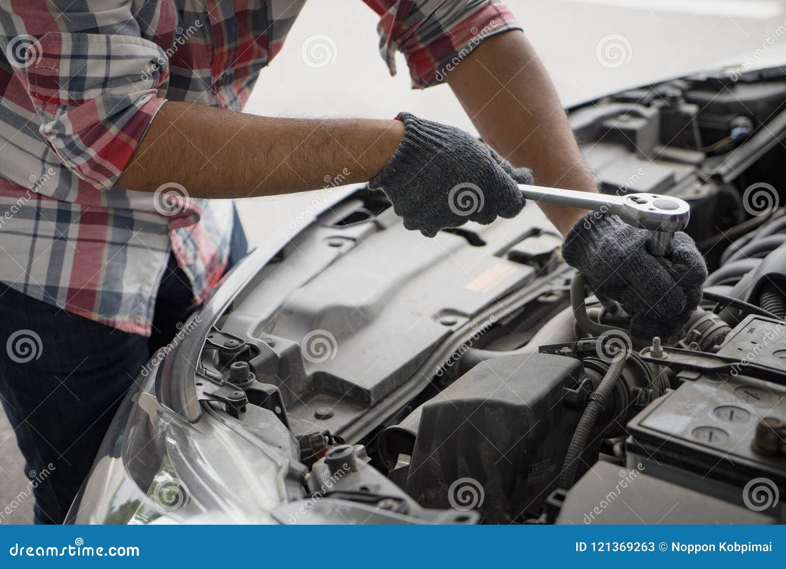 close up mechanical man dirty hands using tool to fix repair car