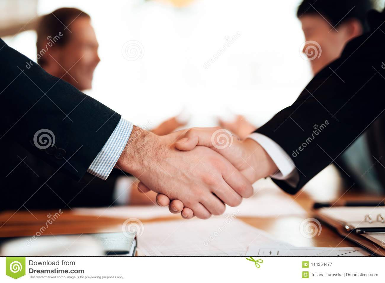 Close up meeting with chinese businessmen in restaurant. Men are shaking hands.