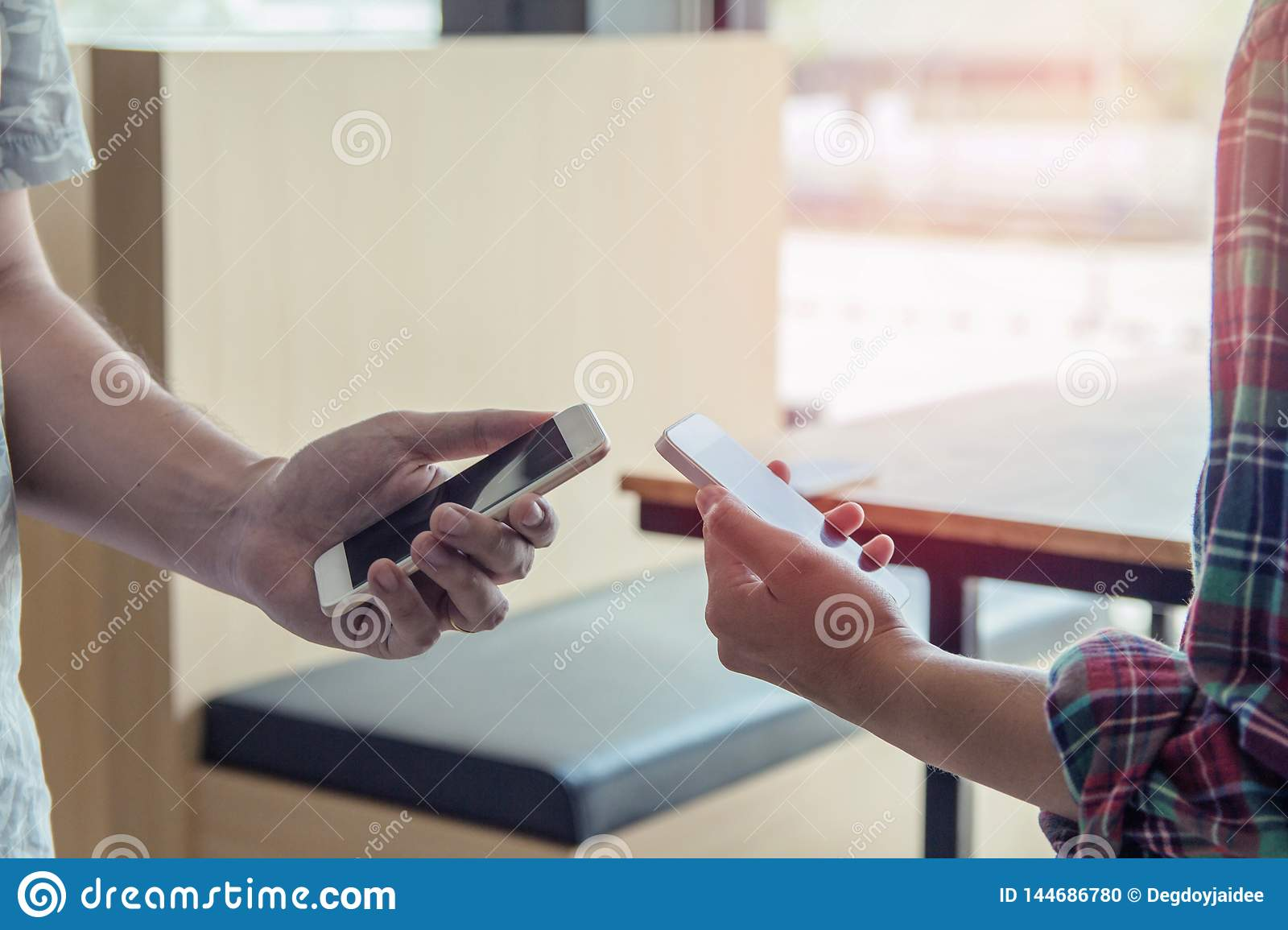 Close up of men and  woman hands holding touching mobile phone with blank copy space for your text
