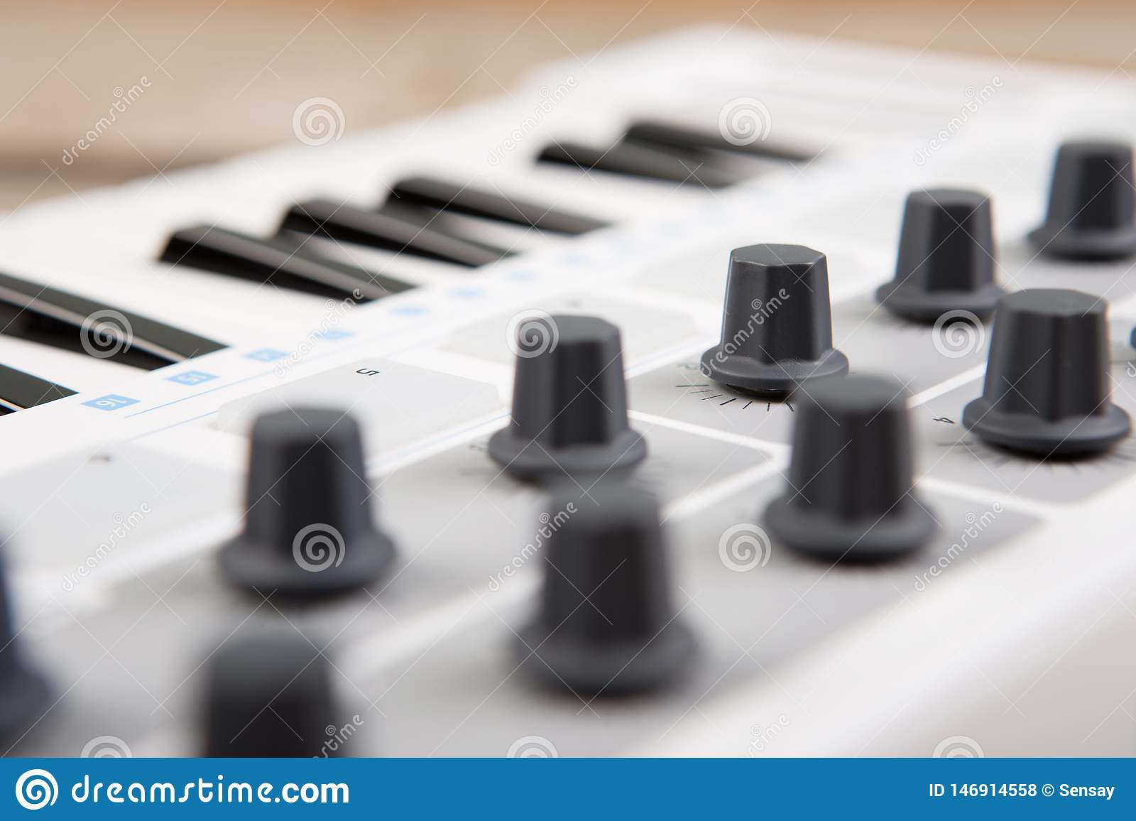 Close up of MIDI controller volume fader, knob and keys