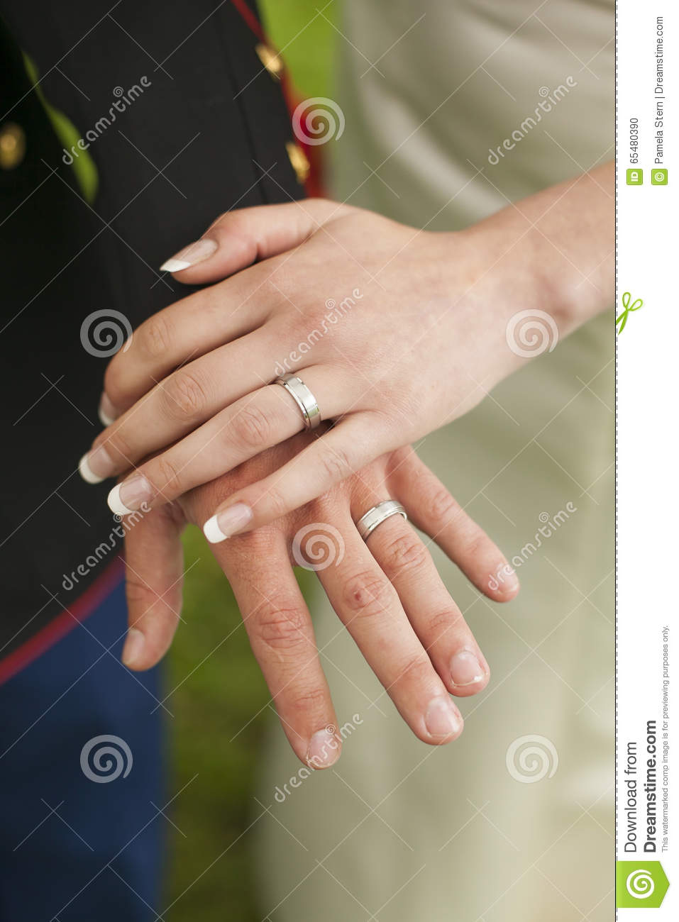 close up of military groom and bride's wedding rings. stock photo