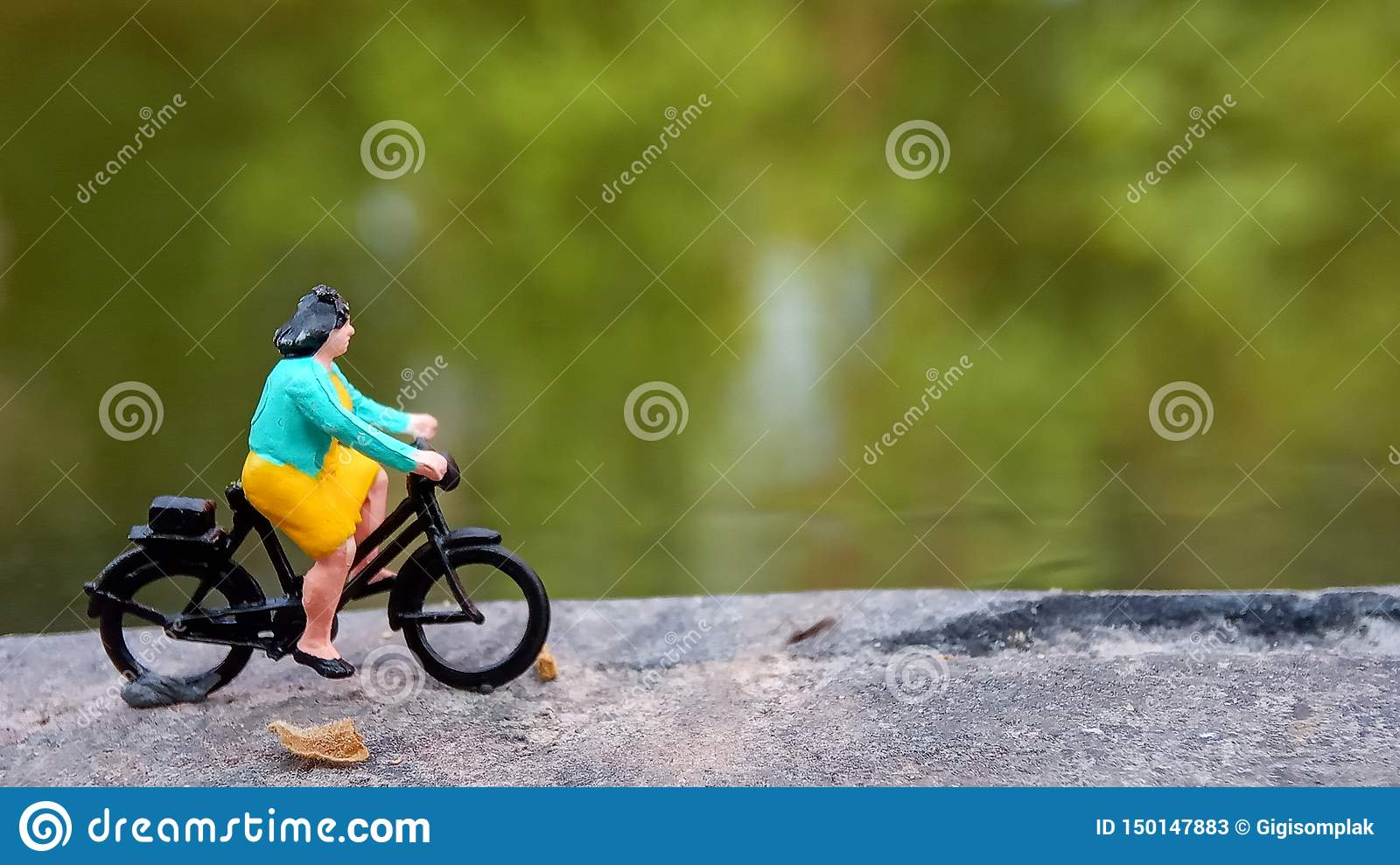 Close up Mini Figure Woman toys bicycling at River Side Path Way with negative or copy space for text area placement