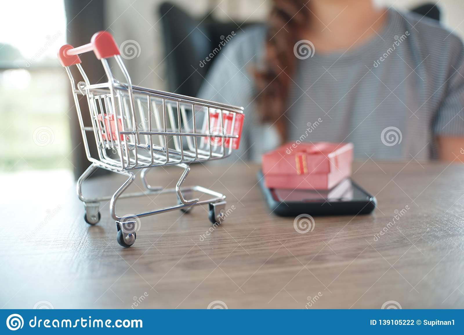 Close up of miniature shopping cart /trolley toy figure. smart phone and red gift box on table for shopping and e-commerce concept