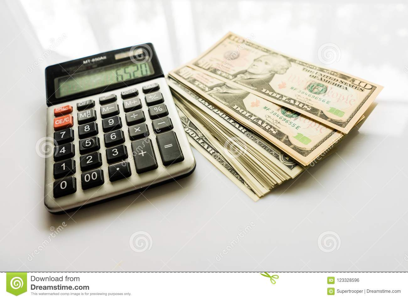 Female hand holding a calculator, and us money on the background.