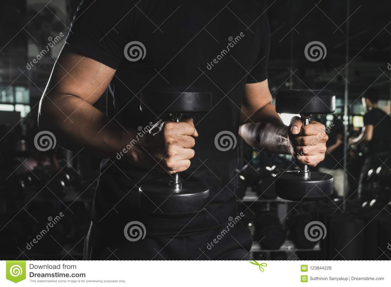 Close Up of a muscular young man lifting weights in gym on dark background.